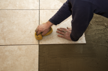 A man installing grout