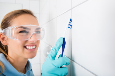 woman cleaning tile with tooth brush